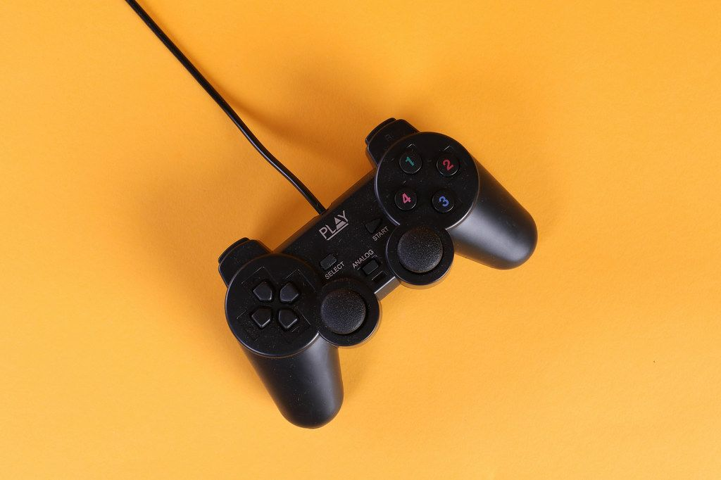Gamepad with a cord on a orange background
