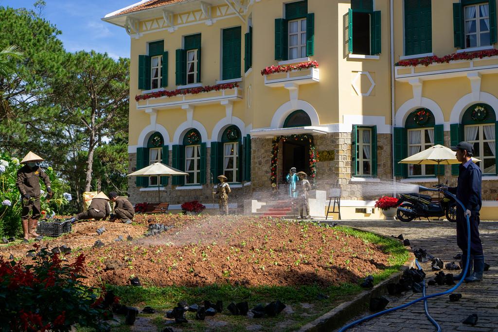 Gärtner bepflanzen und wässern den Garten vor dem Bao Dai Königspalast in Da Lat, Vietnam