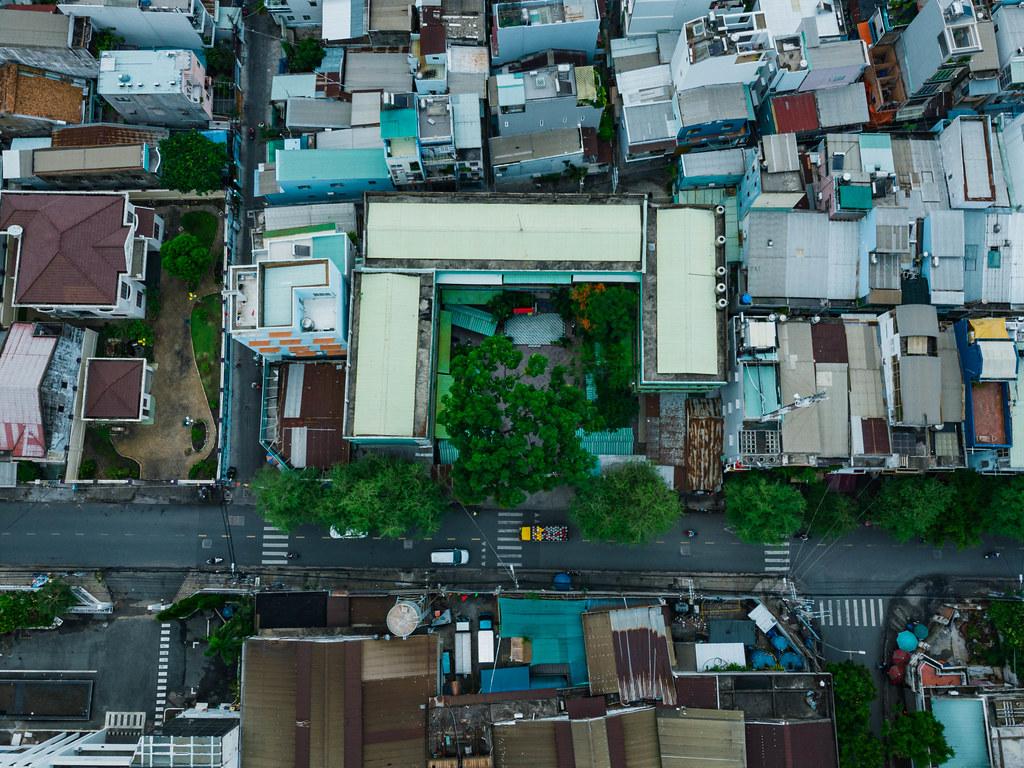 Gebäude, Straßen und Gassen mit Bäumen und Stromleitungen in der Vogelperspektive fotografiert mit einer Drohne in Ho Chi Minh Stadt, Vietnam