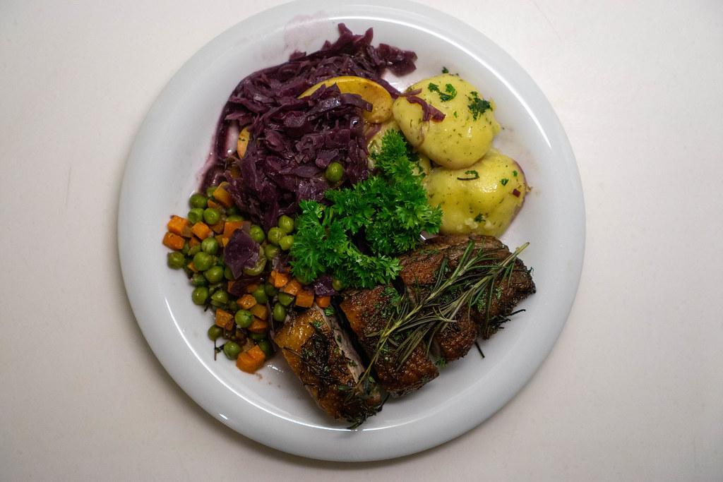 Gebratene Entenbrust mit Rosmarin, Erbsen, Karotten, Apfel-Rotkohl, Kartoffelknödel und Petersilie von oben fotografiert