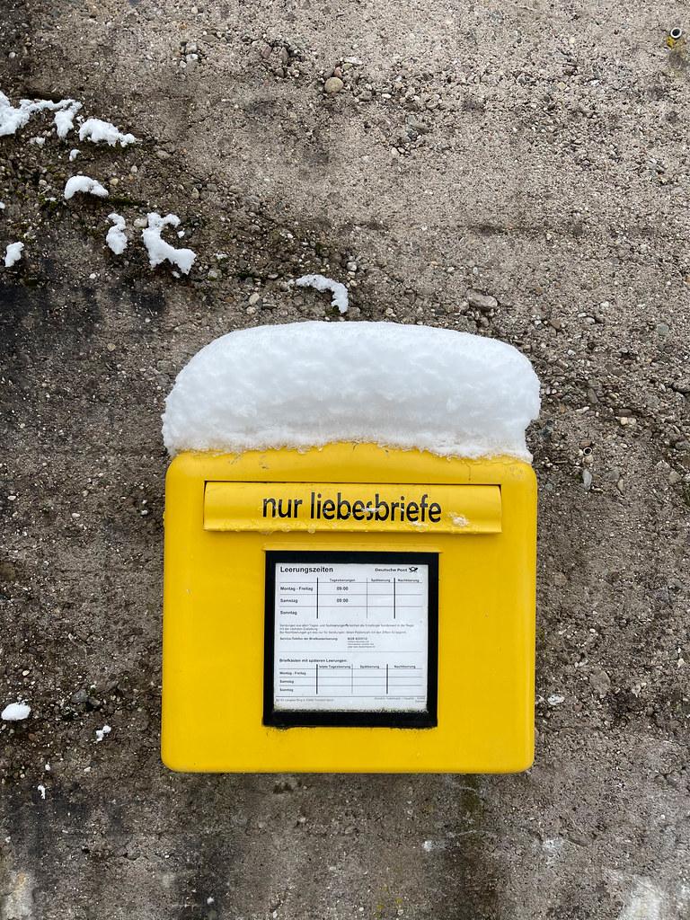 Gelber Briefkasten der Deutschen Post mit einem Aufkleber