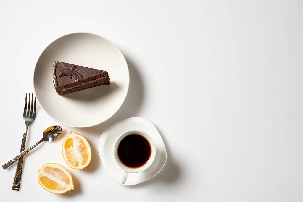 Gemütliche Pause mit Kaffee und Torte: Aufnahme von oben mit angeschnittener Zitrone und Besteck