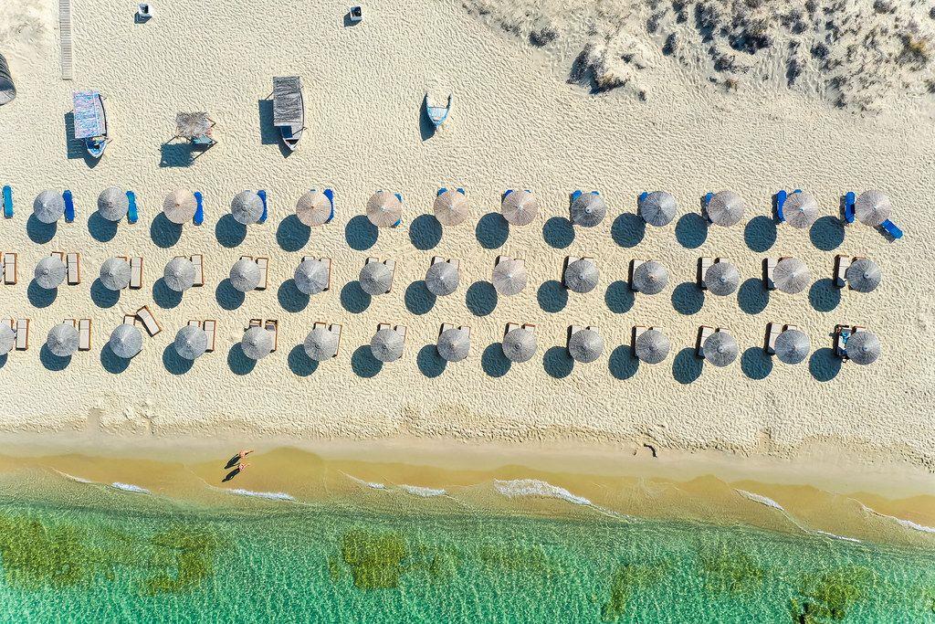 Geometrie am Strand: Overhead Luftbild von Sonnenschirmen aus Stroh. Plaka, Naxos