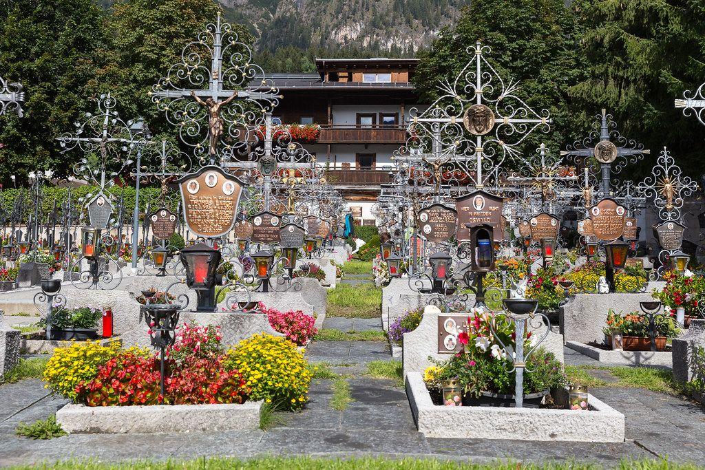 Gepflegter Friedhof in Alpbach mit Blumen und Grabsteinen mit Metallkreuzen und Fotos der Toten