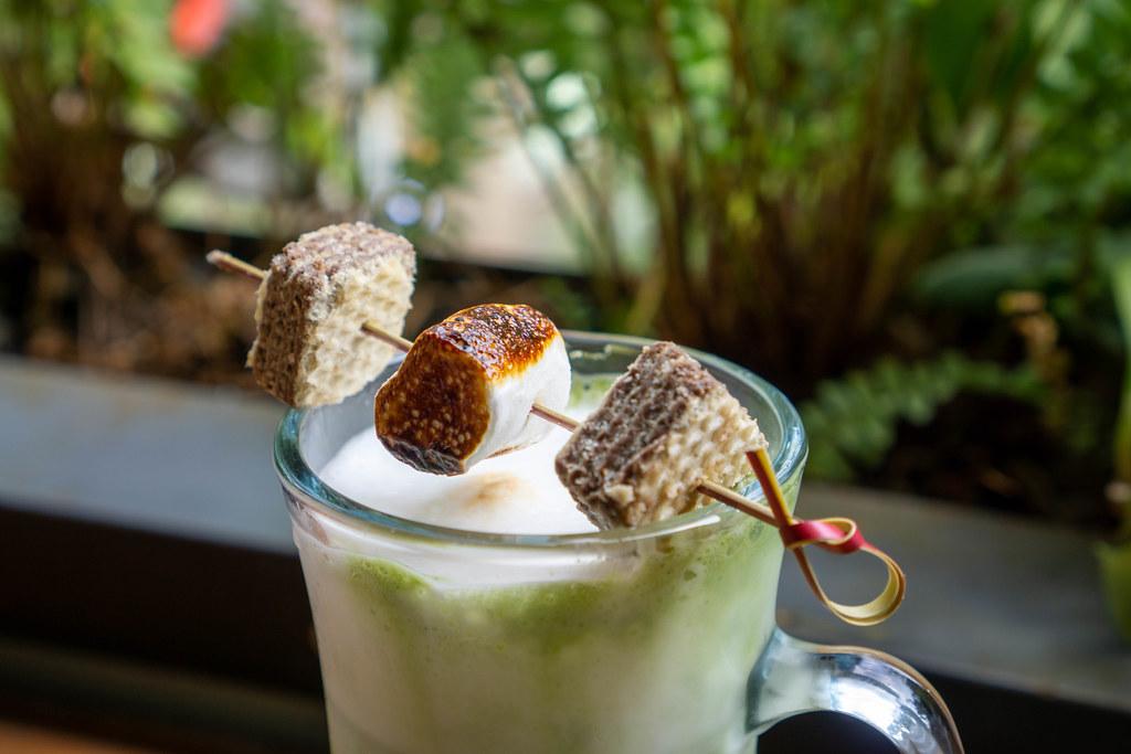 Geröstetes Marshmallow auf einem Holzspießchen mit Keksen auf einem Kaffeeglas mit Latte Macchiato Nahaufnahme