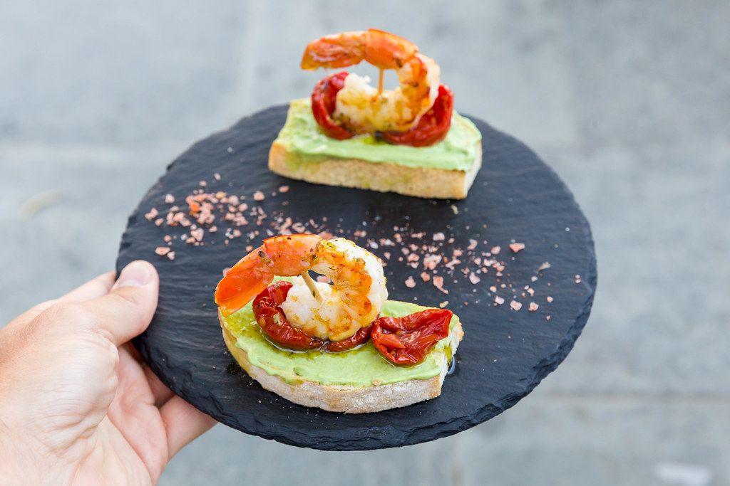 Geröstetes Brot, King Prawns, Avocado-Aufstrich, getrocknete Tomaten auf einem runden Brett bei Q11