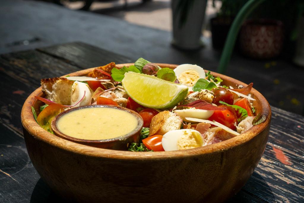 Gesunde Salat Bowl mit Hähnchen, gekochten Wachteleiern, Kirschtomaten, Parmesan Käse, Basilikum, Geröstetem Brot, Limette und Honig-Senf Sauce in einer Holzschüssel Nahaufnahme