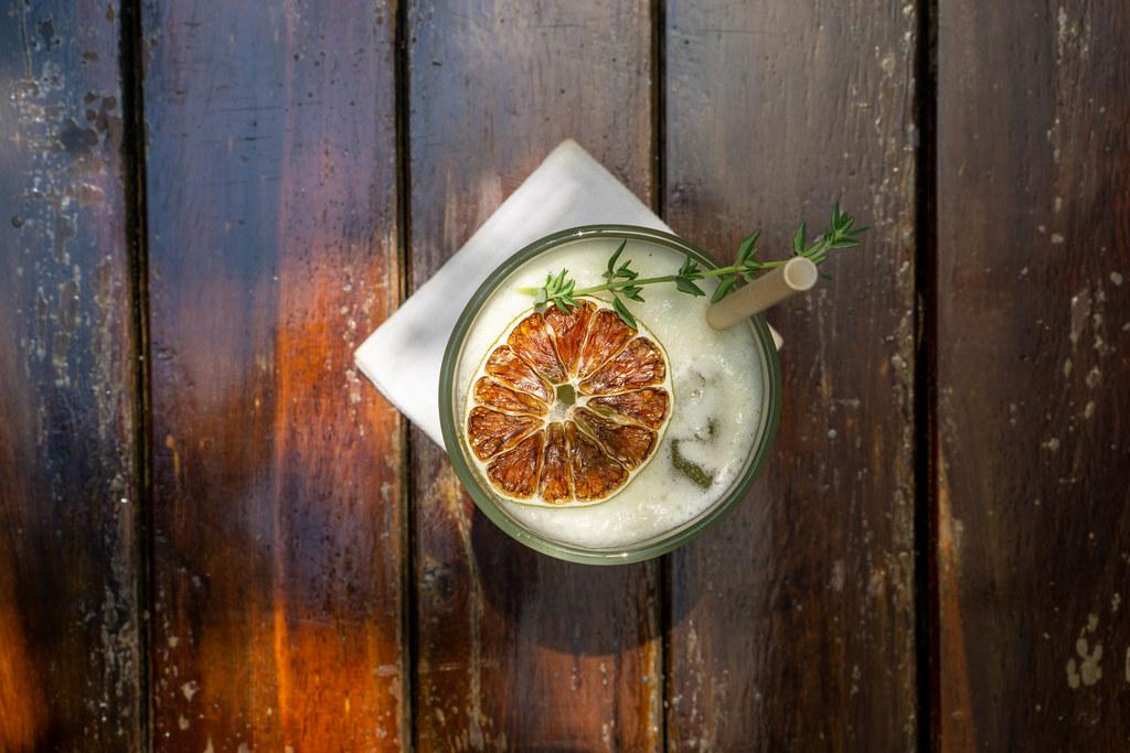 Getrocknete Orangenscheibe und Rosmarin in einem Fruchtsaft mit Eiswürfeln und Papier-Strohhalm von oben auf einem Holztisch fotografiert