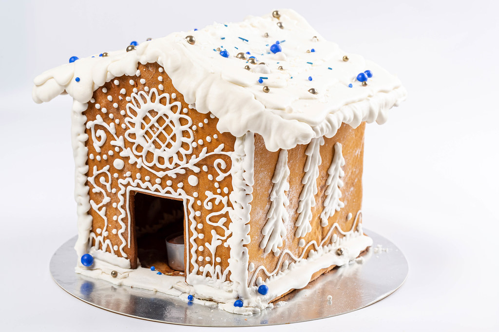 Gingerbread house with glaze ornament on white background