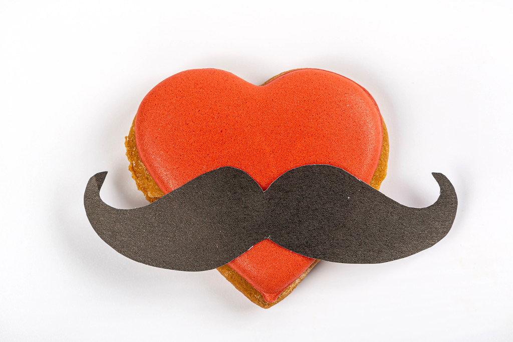 Gingerbread valentine heart with red icing and black mustache on white background
