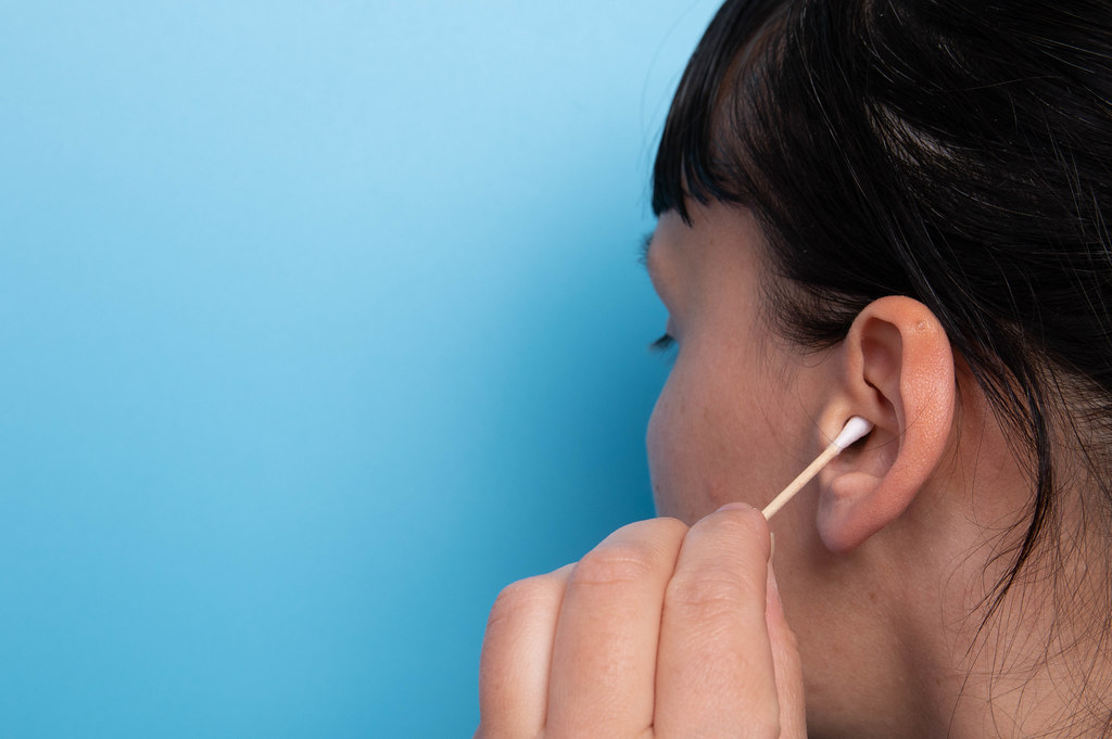Girl cleaning her ear with a cotton swab