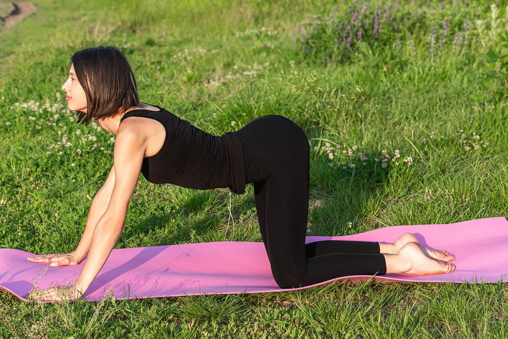 Girl in cat pose (marjariasana) doing yoga
