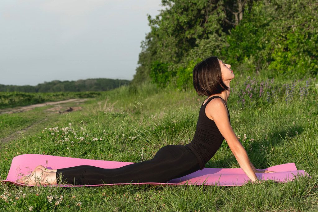 Girl in dog pose face up in summer on nature (urdhva mukha schwanasana)