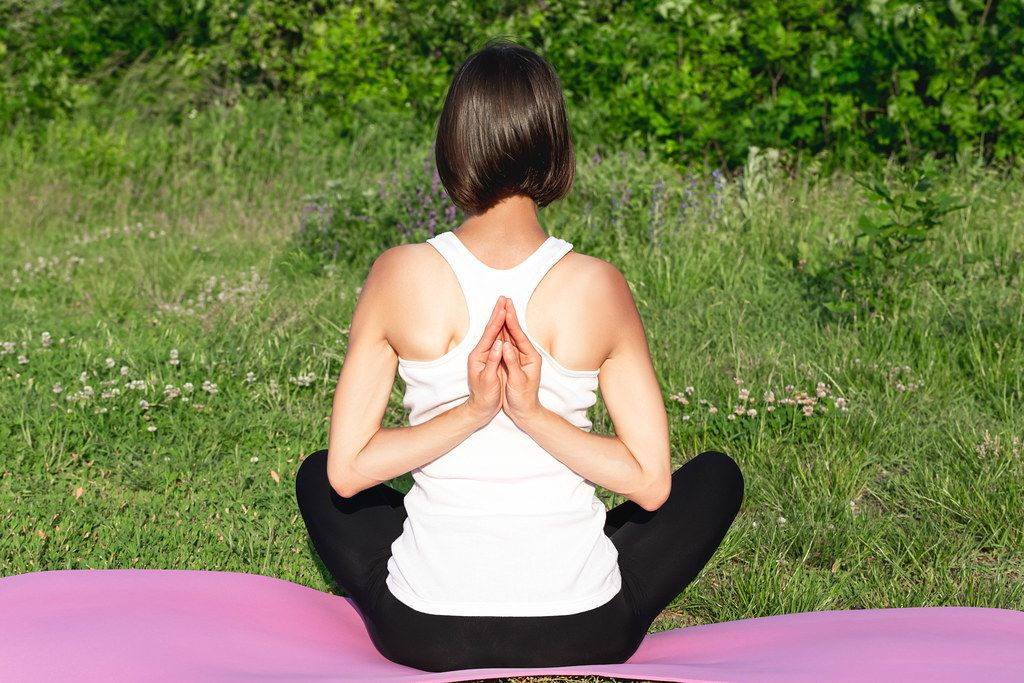 Girl meditates in Pashchim Namaskarasan pose - reverse prayer position