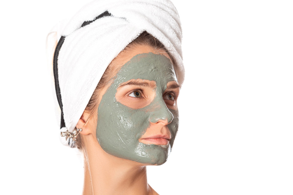 Girl with facial clay mask, beauty treatments