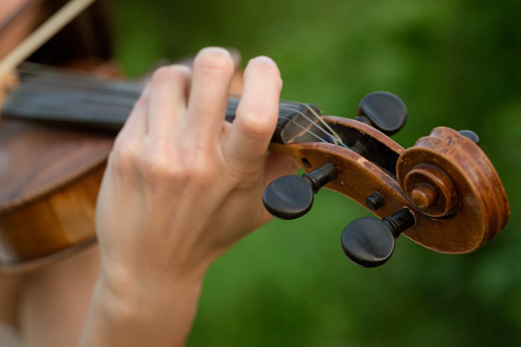 Girl's hand on the strings of a violin, close up
