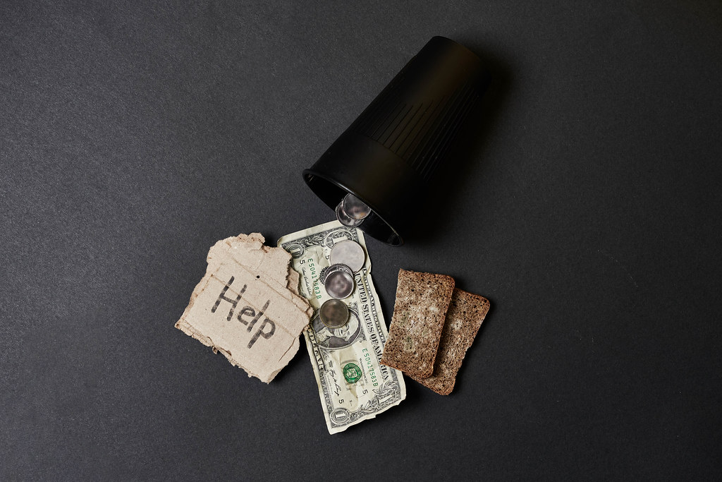 Giving money to beggar or homeless - poverty and social issue concept