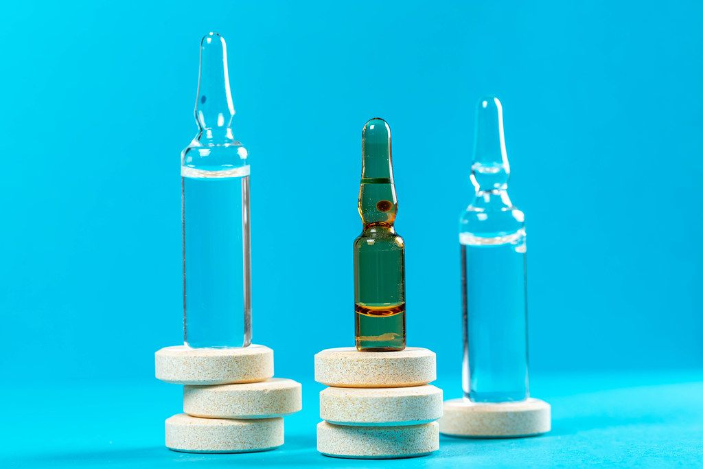 Glass ampoules with large round pills on blue background