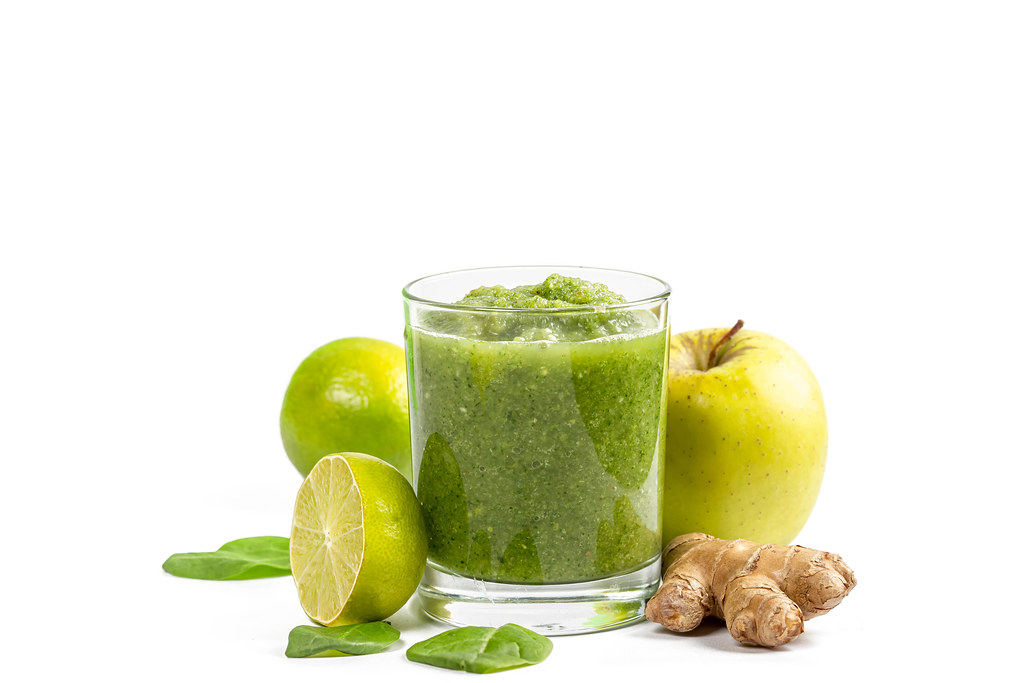 Glass of green smoothie with apple, lime, ginger root and spinach leaves