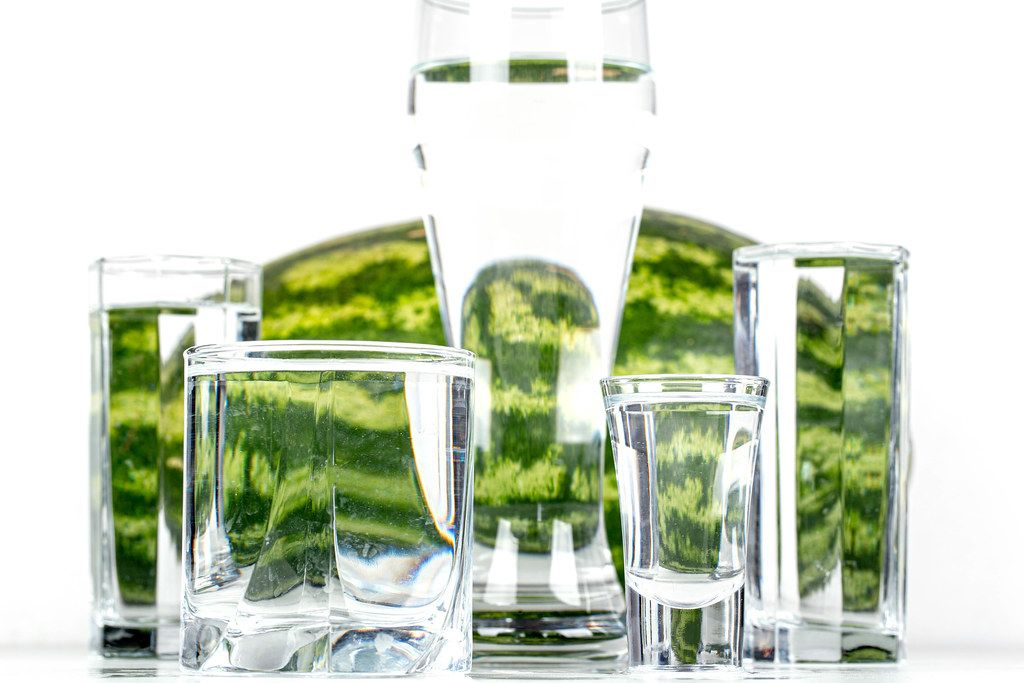 Glasses of different sizes with water with watermelon in the background