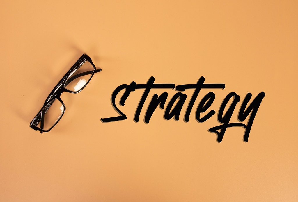 Glasses with Strategy text on orange background