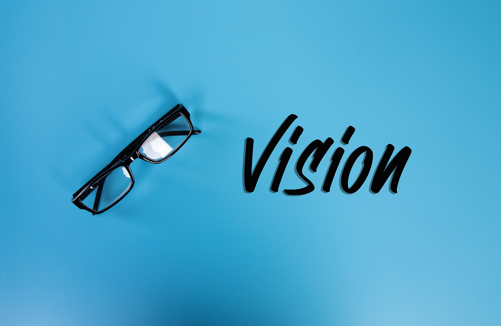 Glasses with Vision text on blue background