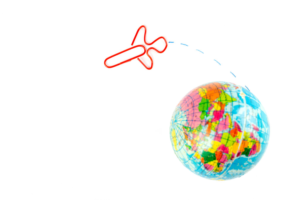 Globe model with airplane paper clip flying on the white background, transport and travel concept