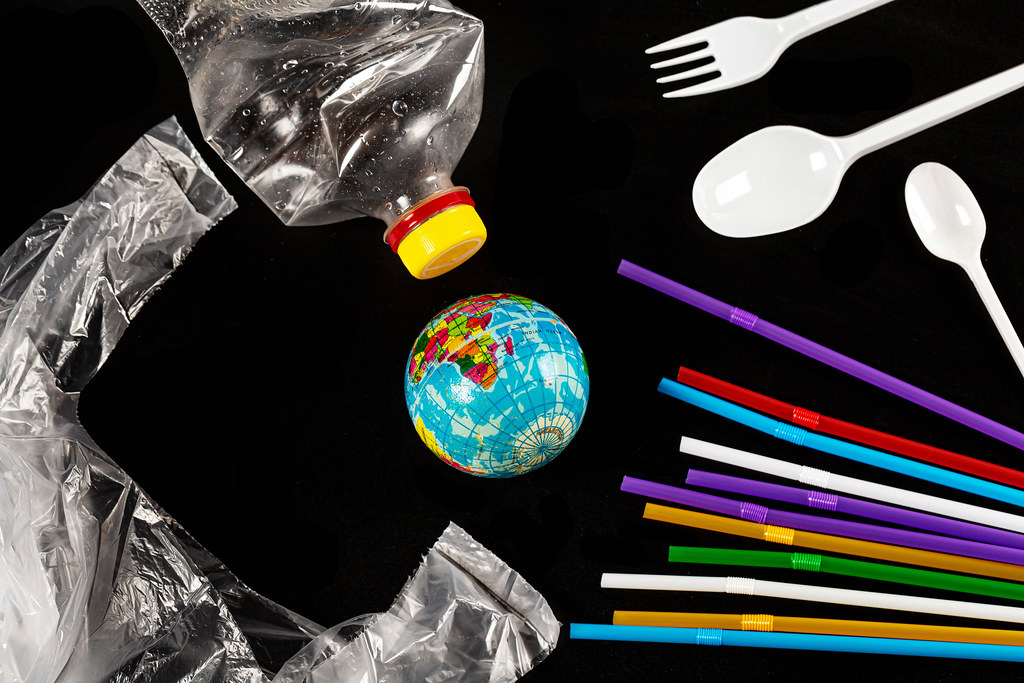 Globe, plastic disposable tableware, bottle and package on black background, planet garbage pollution concept
