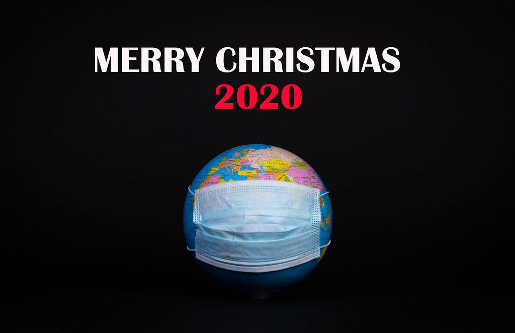 Globe with face mask and Merry Christmas 2020 text on black background