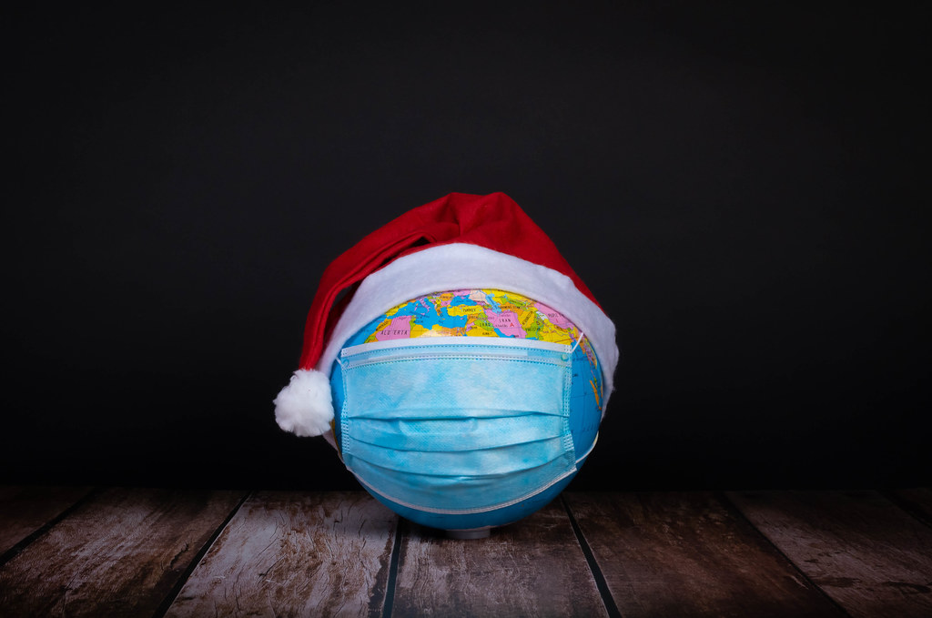 Globe with face mask and red Christmas hat on black background