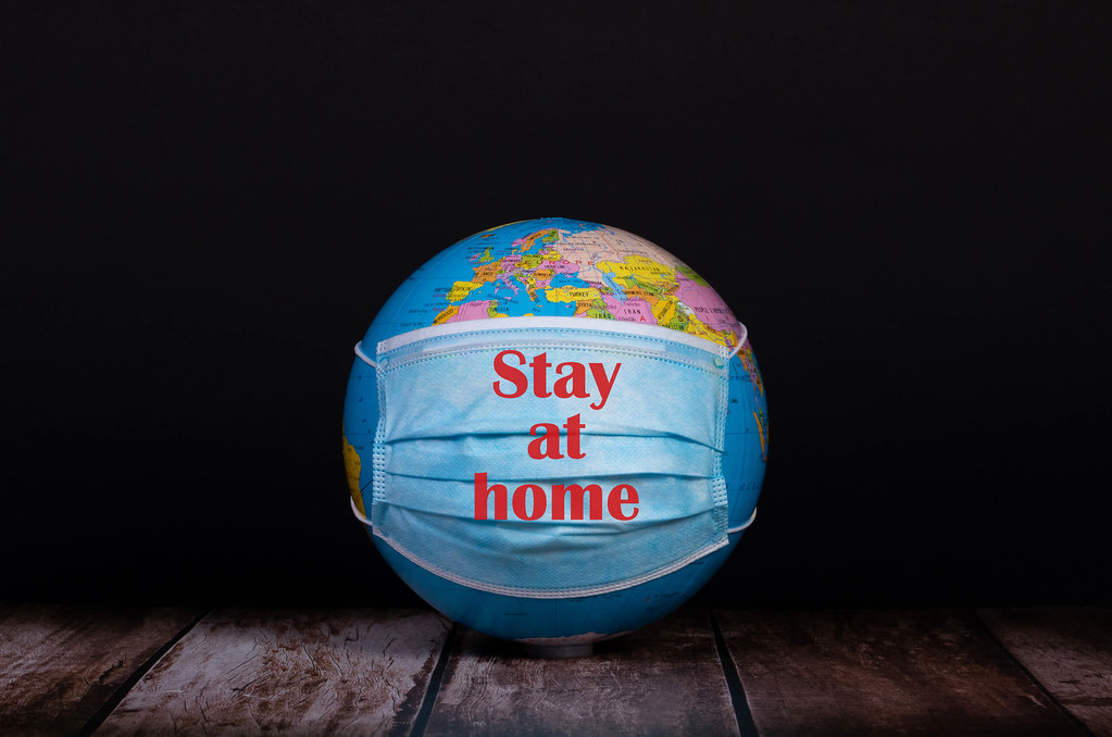 Globe with face mask and Stay at home text