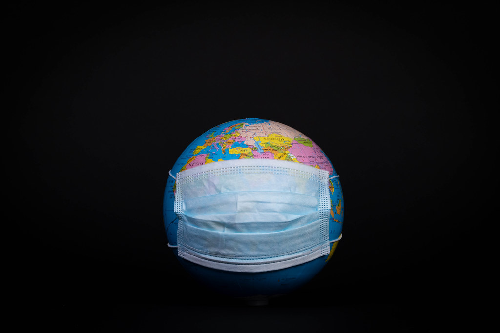 Globe with face mask on black background