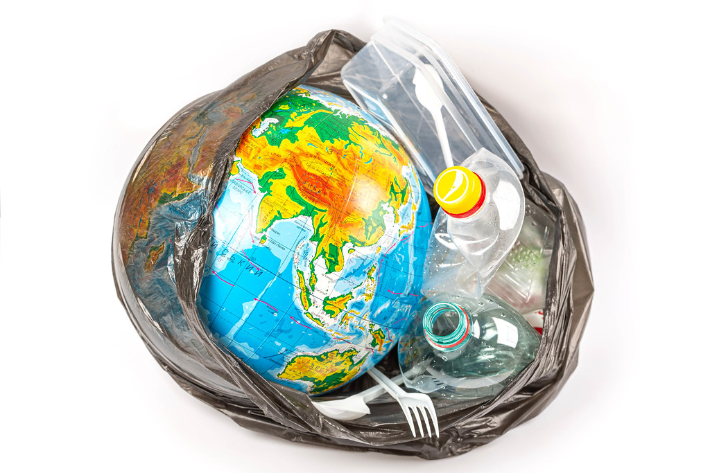 Globe with plastic utensils in black trash bag, planet pollution concept