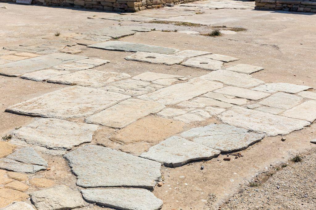 Gneis-Platten auf dem Boden der Agora der Kompetaliastae. Antiker Marktplatz auf Delos