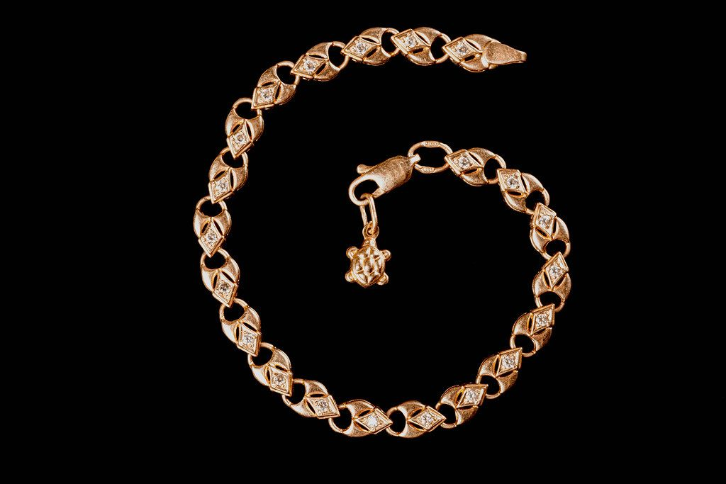 Gold bracelet of hearts with a turtle pendant on a black background