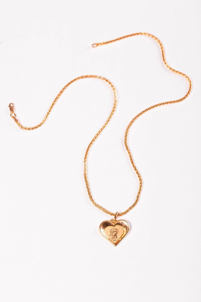 Gold chain and pendant in the shape of a heart on a white background