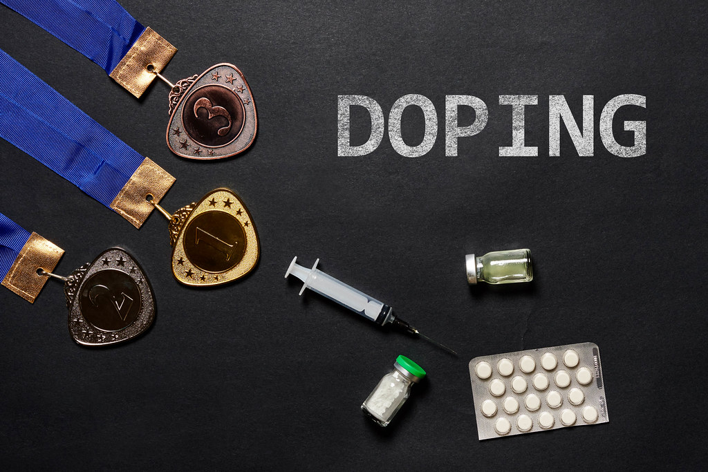 Gold, silver and bronze medal and doping syringe and pills on a dark background