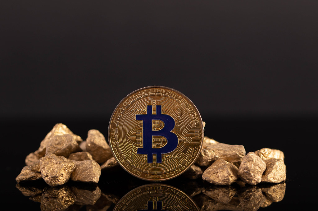 Golden Bitcoin and gold nuggets on black background