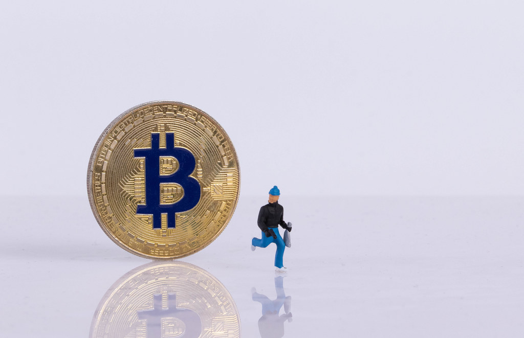 Golden Bitcoin and robber on white background