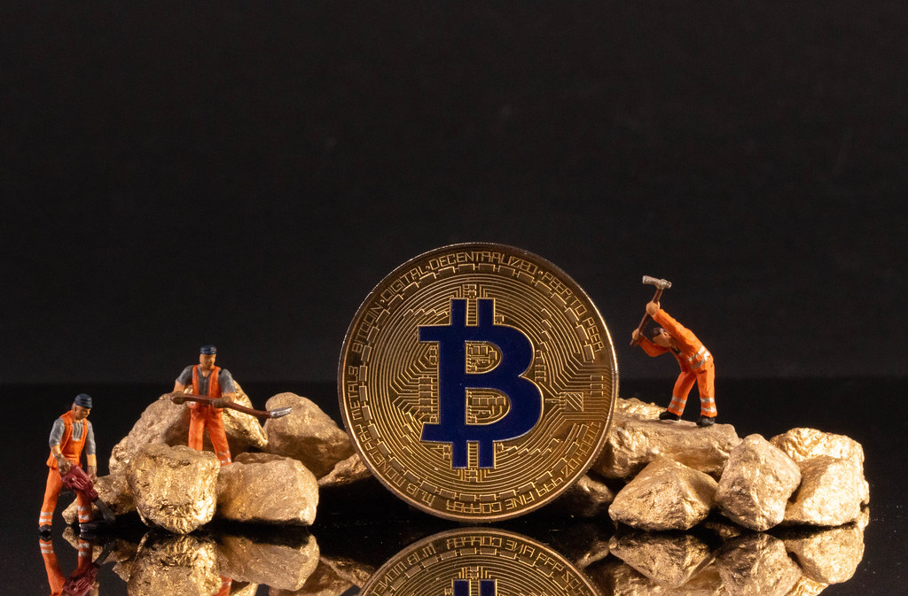 Golden Bitcoin, gold nuggets and miniature workers on black background