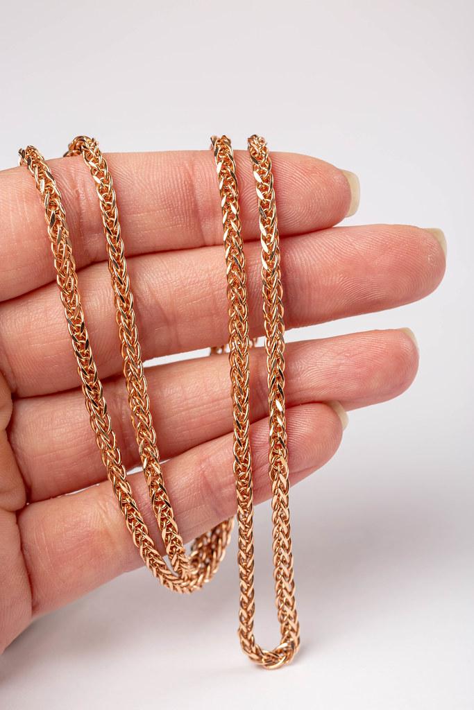 Golden chain in women hand on white background