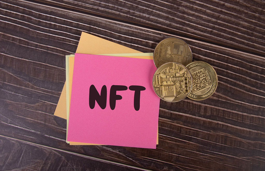 Golden coins and sticky notes with NFT text on wooden table