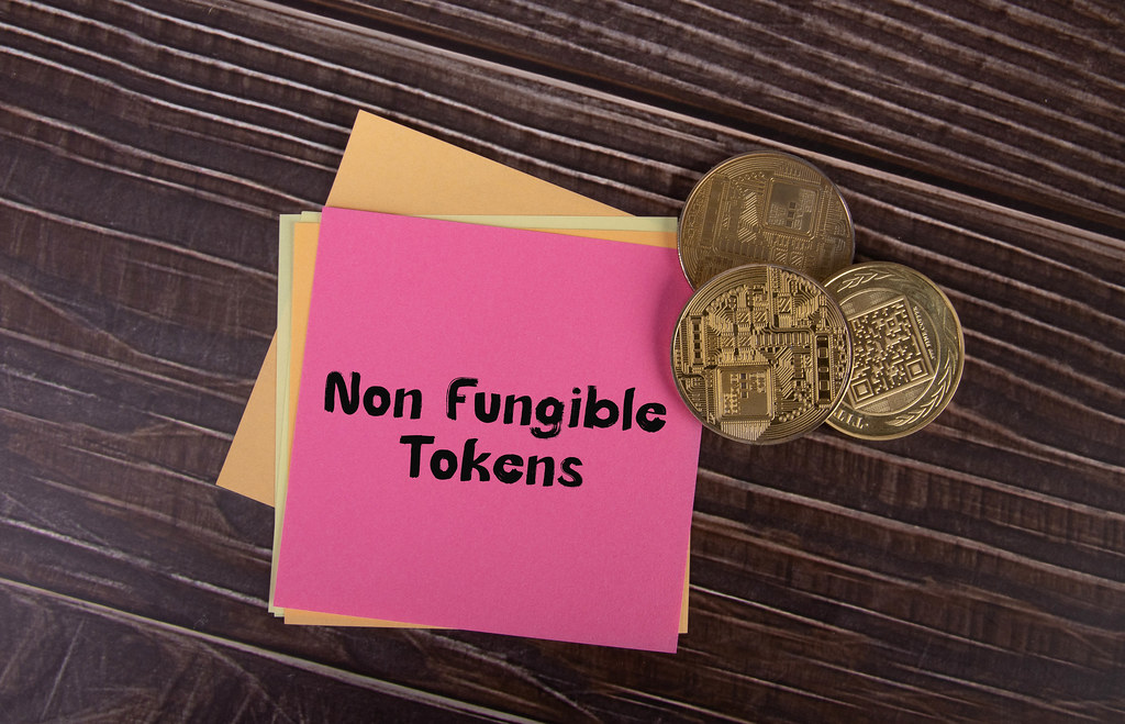 Golden coins and sticky notes with Non Fungible Tokens tex