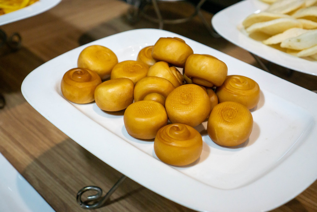 Golden Deep Fried Mantou and Shrimp Chips on Large White Plates at a Catering Buffet in an Asian Restaurant