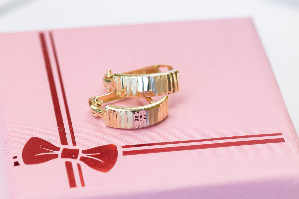 Golden earrings on the pink present box  with bow