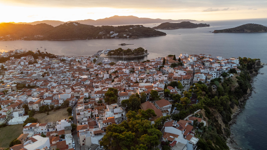 Golden hour on the Greek island of Skiathos, aerial view of the town with white houses and red roofs