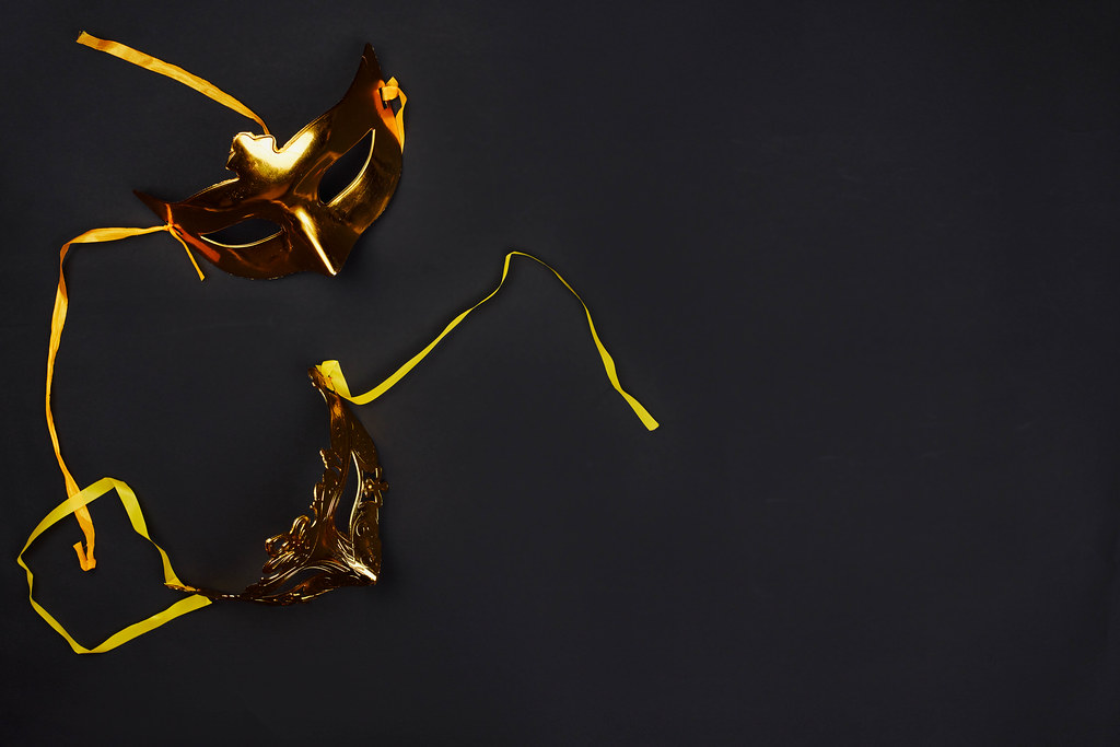 Golden Mardi Gras masks on dark background