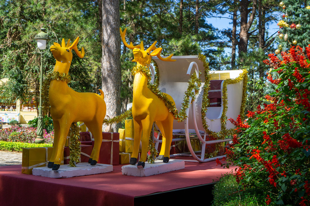 Golden Reindeer with White Sleigh, Christmas Tree and Presents as Christmas Decorations in a Park at Sunny Weather.