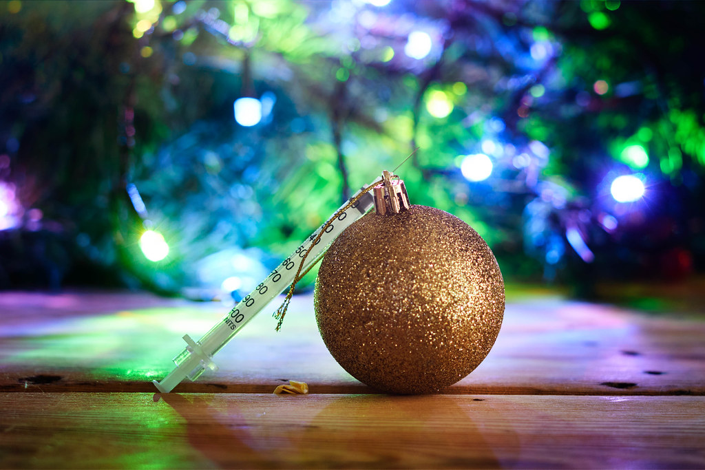Golden textured Xmas bauble over decorated Christmas tree