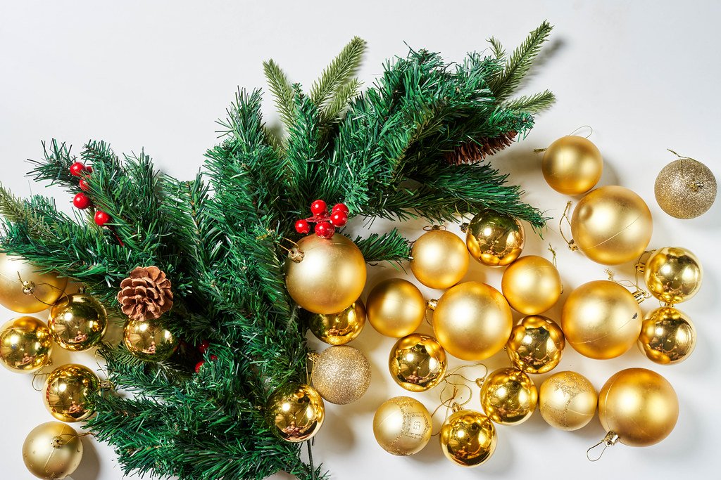 Golden Xmas baubles and evergreen tree branches from above
